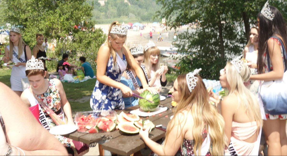 Miss Teen Calgary cutting watermelon for the masses at the beach